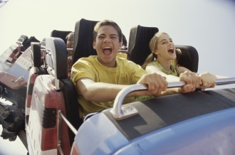 Teenage couple riding a rollercoaster and screaming
